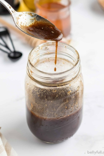 Balsamic Vinegar Dressing dripping off of spoon into jar