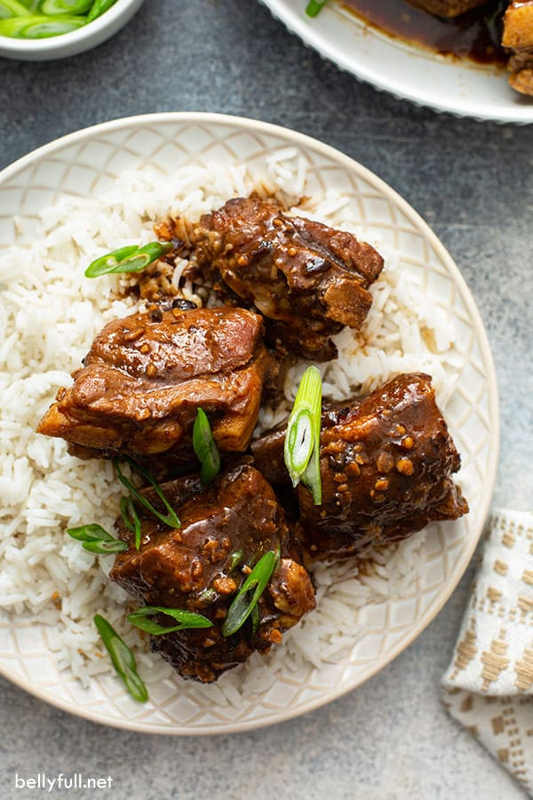 4 Chinese spare ribs over white rice on ornate plate