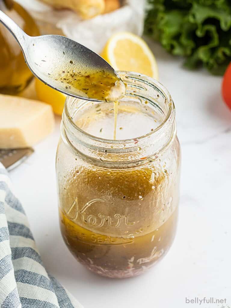 Italian dressing dripping off spoon into glass jar