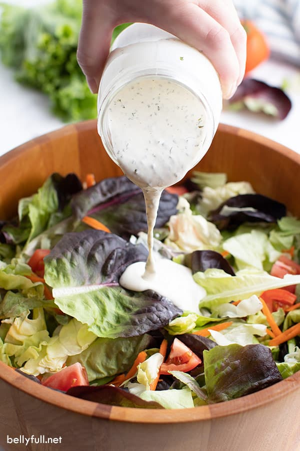 ranch dressing pouring out of jar onto salad