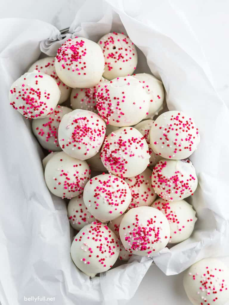 Pile of Red Velvet Cake Truffles with white chocolate and pink sprinkles