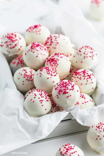 cake balls coated in white chocolate and pink sprinkles