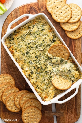overhead of spinach and artichoke dip in baking dish with crackers