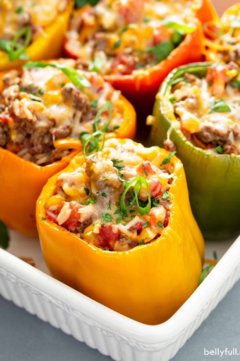 cooked stuffed peppers in white baking dish