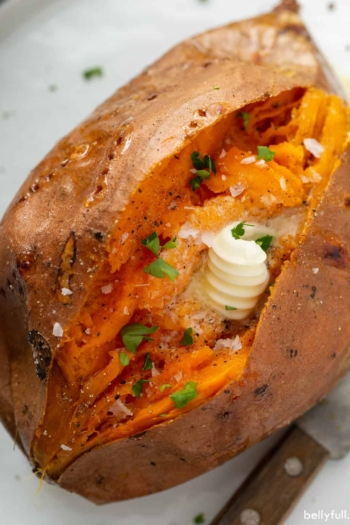 close up of baked sweet potato sliced open with butter and pepper