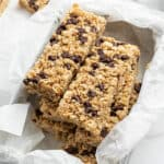stacked homemade granola bars in parchment lined tray