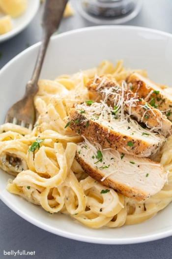 close up of chicken alfredo on white plate