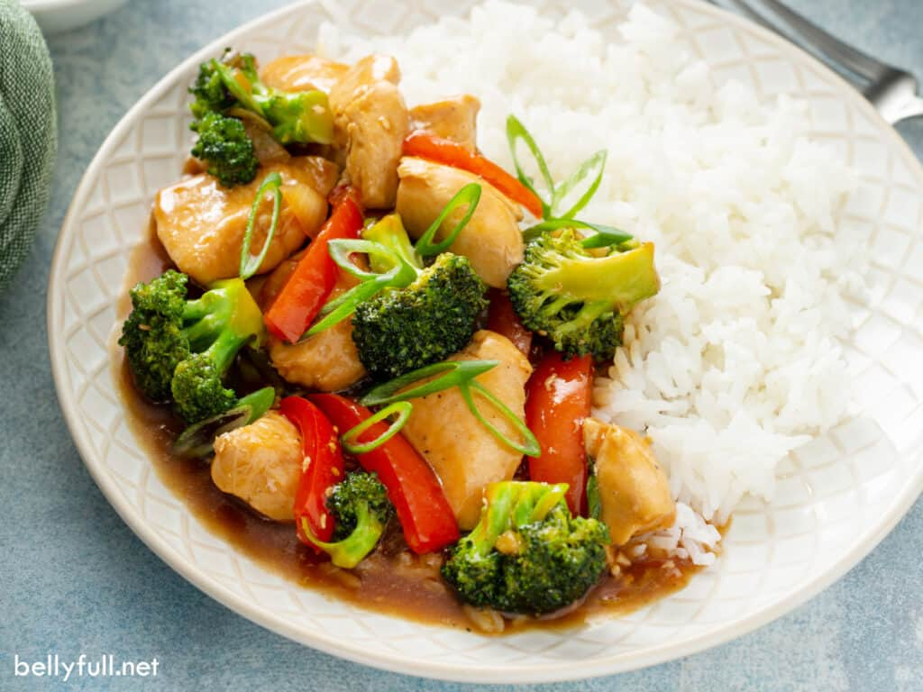 Chicken stir fry over white rice on plate