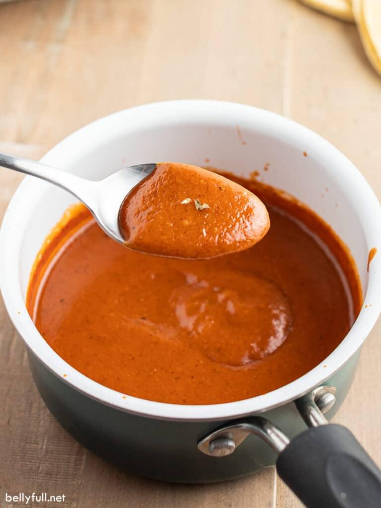 homemade enchilada sauce on spoon over saucepan