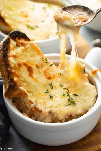 french onion soup in white bowl with cheese pull