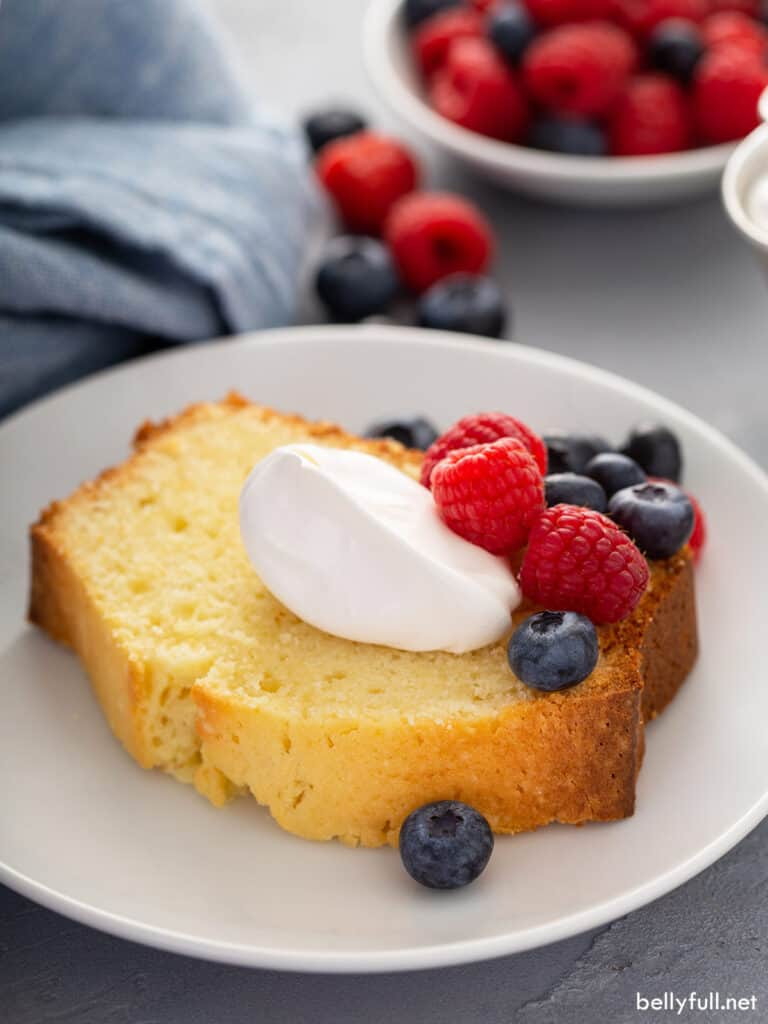 slice of pound cake on plate with whipped cream and fresh berries