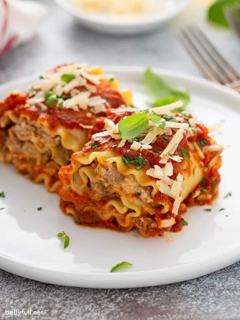baked sausage lasagna rolls on white plate