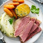 overhead 3 slices corned beef with vegetables on white plate