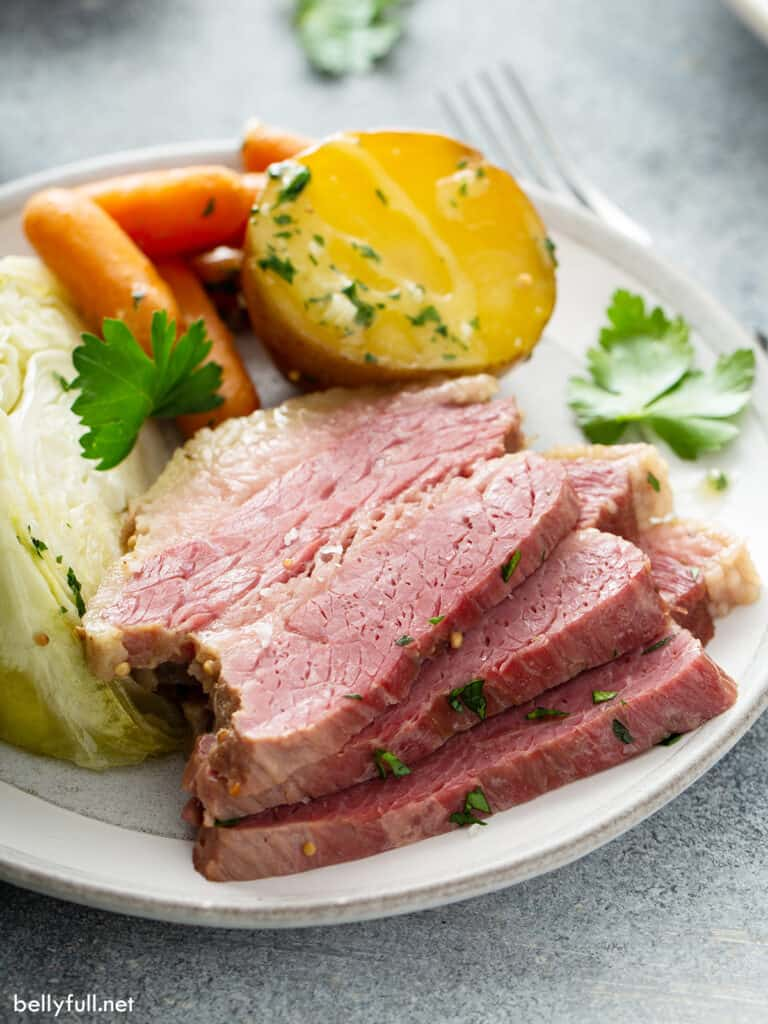 3 stacked slices of corned beef on white plate with vegetables
