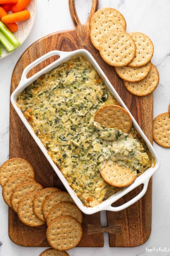 overhead of baked spinach artichoke dip in white casserole dish