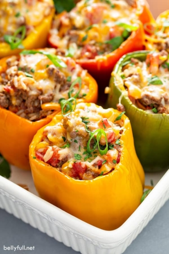 close up of stuffed peppers in white baking dish