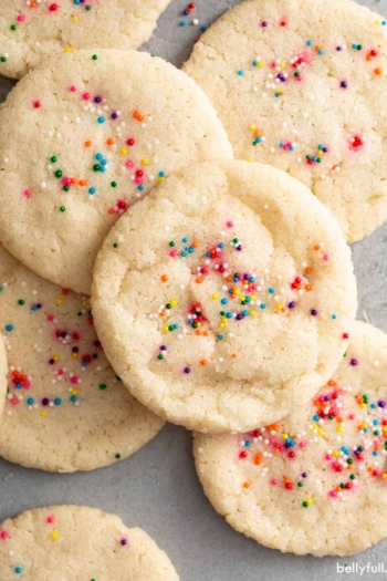 close up overhead of sprinkled baked sugar cookies in a pile