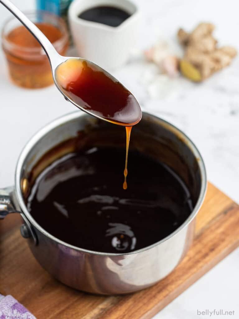 Teriyaki sauce dripping off of spoon into saucepan