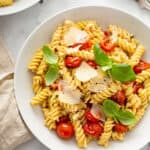 rotini pasta with cherry tomatoes and shaved parmesan in white bowl
