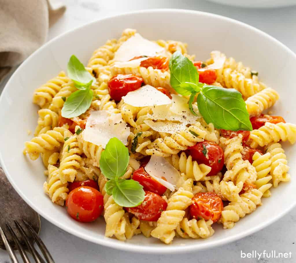 feta and tomato pasta with fresh basil leaves in bowl