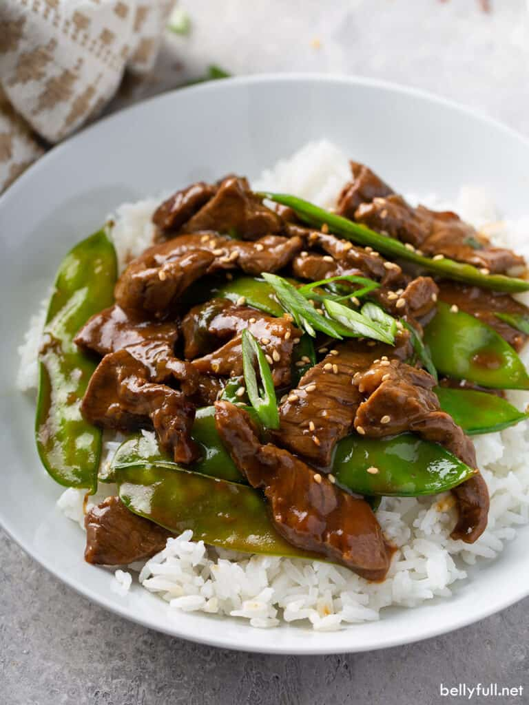 stir fry beef with snow peas over white rice in bowl