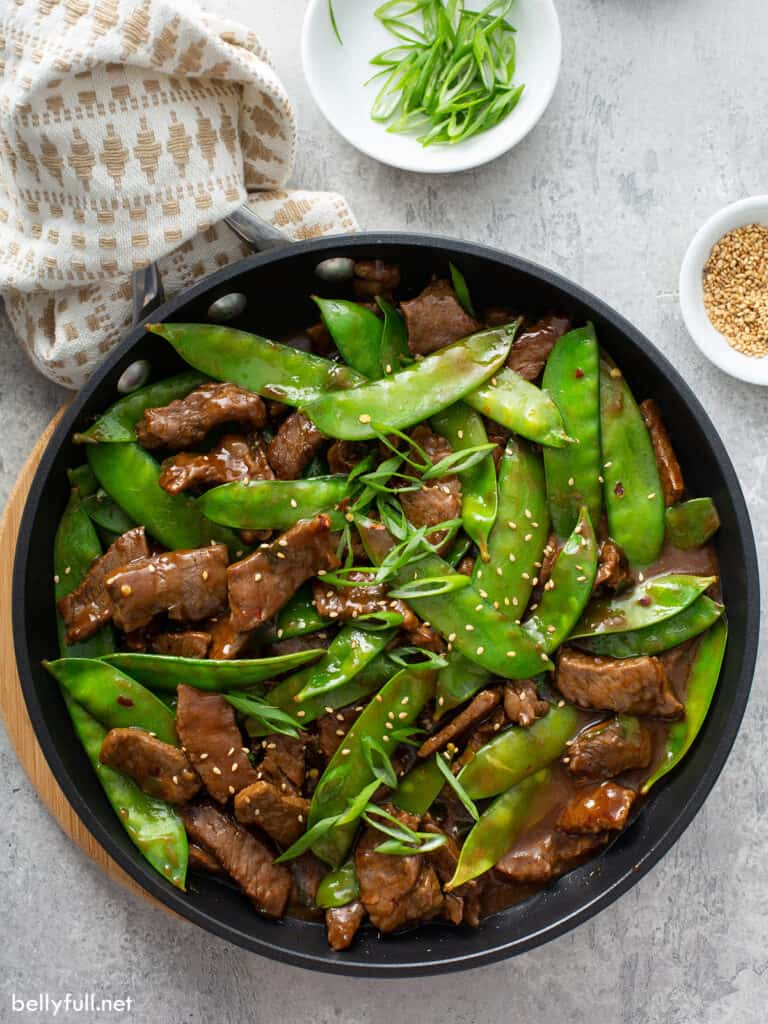 overhead beef stir fry with snow peas in skillet