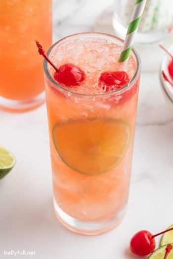 cherry limeade in glass with maraschino cherries and a lime slice