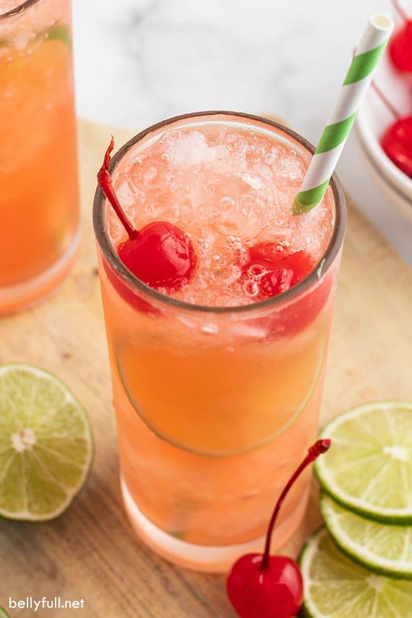 soda, crushed ice, and maraschino cherries in tall glass