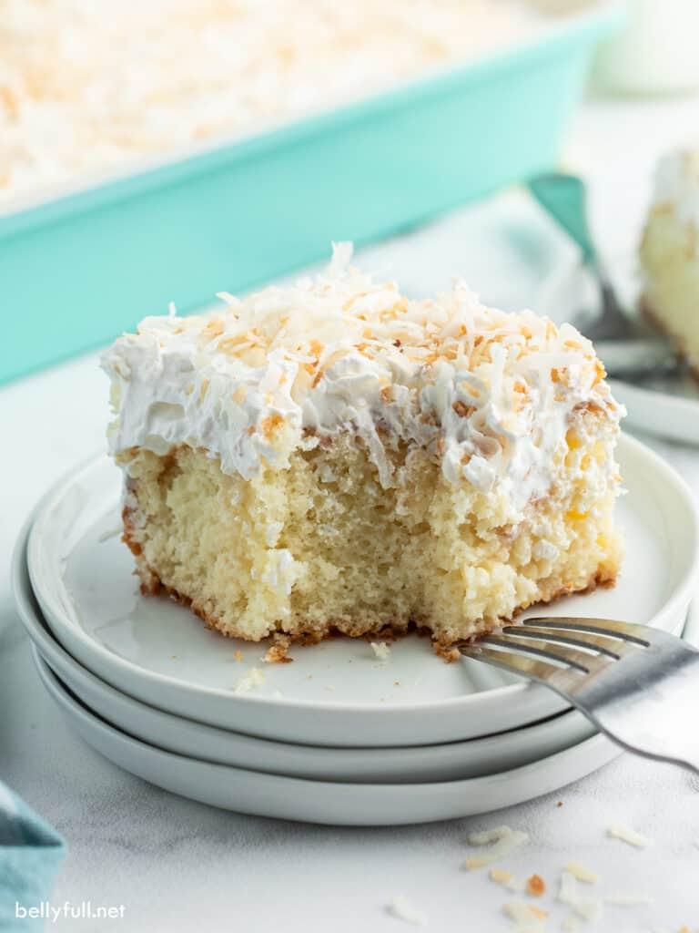 slice of coconut poke cake on white plate