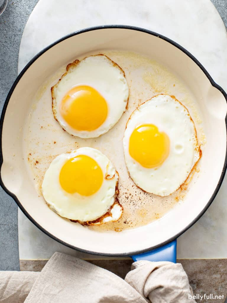 3 sunny side up fried eggs in cast iron pan