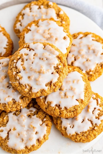 overhead picture stack of iced oatmeal cookies on white plate