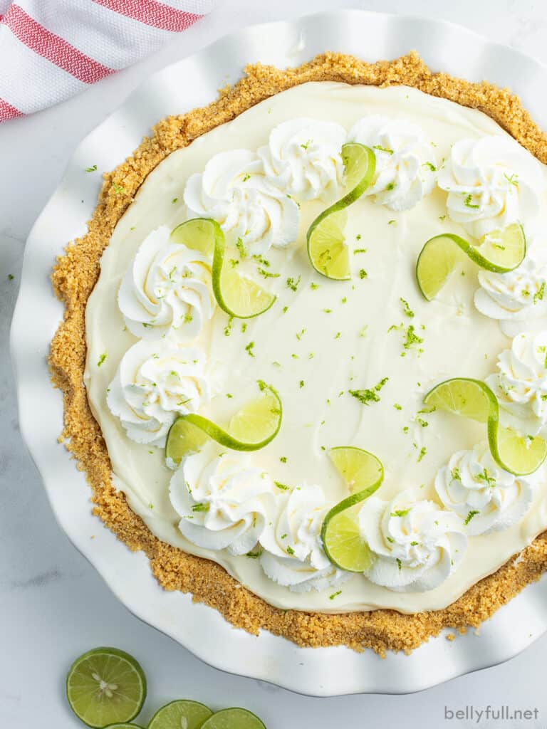 overhead key lime pie garnished with whipped cream and key lime slices