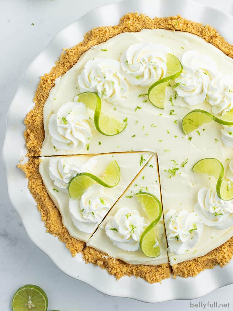 whole lime pie with two slices cut