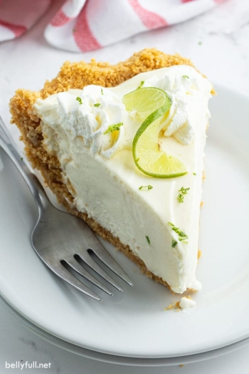 slice of key lime pie on white plate with fork