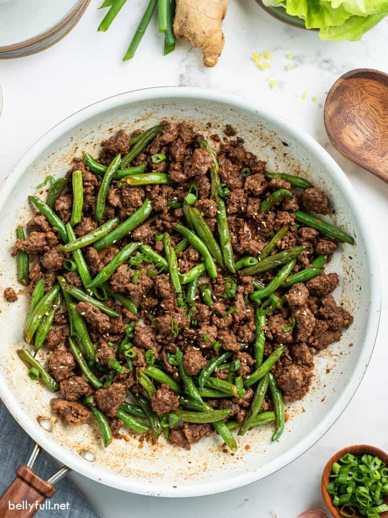 Ground beef crumbles with green beans in white skillet overhead