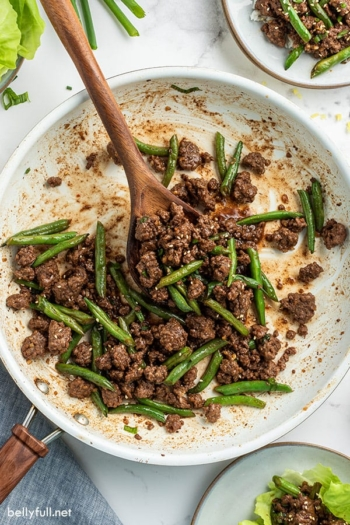 Ground beef with green beans and wooden spoon in skillet