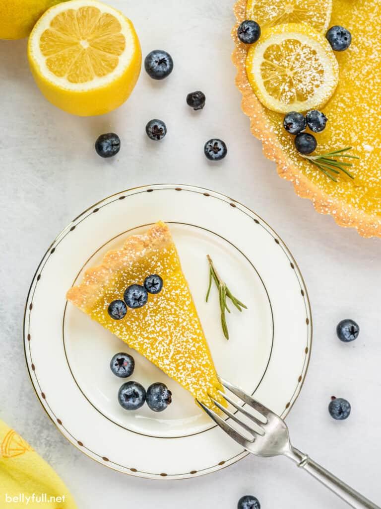 lemon tart slice on plate with blueberries