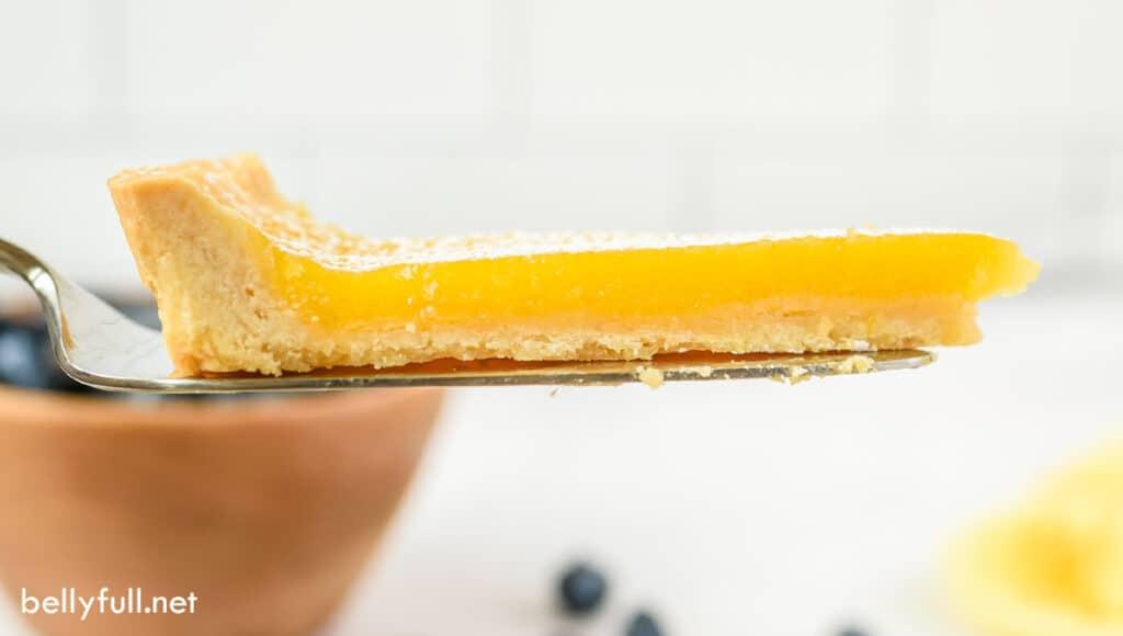 side angle of lemon tart slice on metal serving spatula