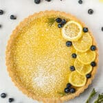 whole lemon tart garnished with lemon slices, blueberries, and powdered sugar