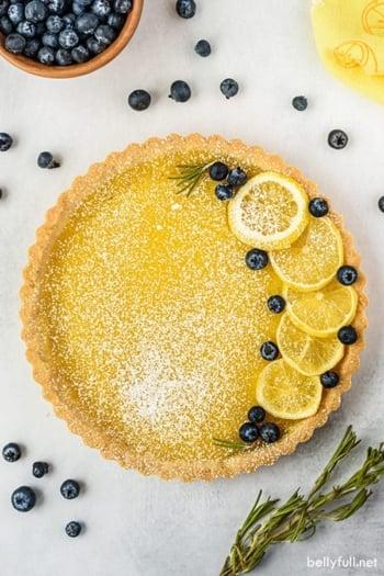 whole lemon tart garnished with lemon slices, blueberries, and powdered sugar