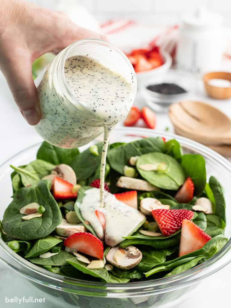 poppy seed dressing being poured over salad