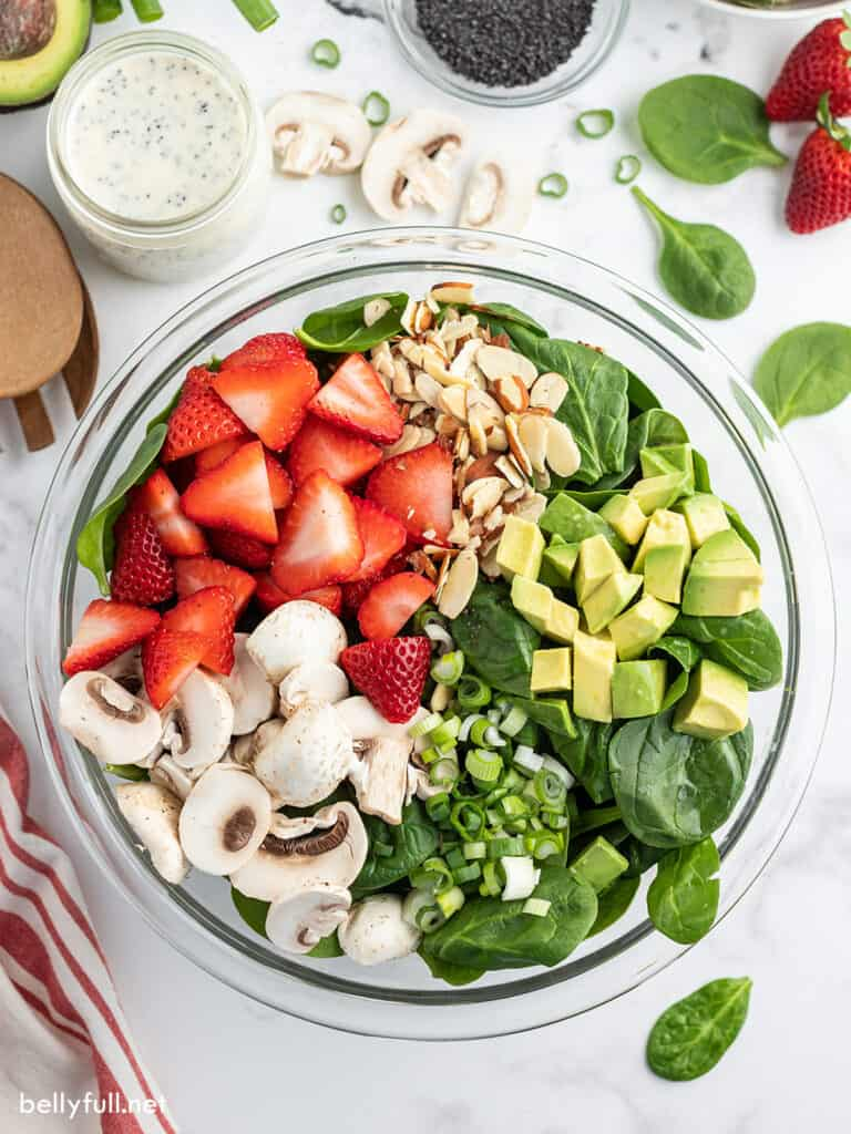 overhead strawberry spinach salad ingredients in glass bowl