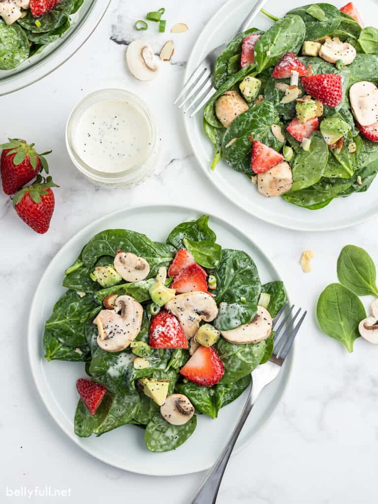 portion of spinach salad with poppy seed dressing on plate with fork