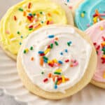 cookie with white sugar cookie frosting and sprinkles on plate