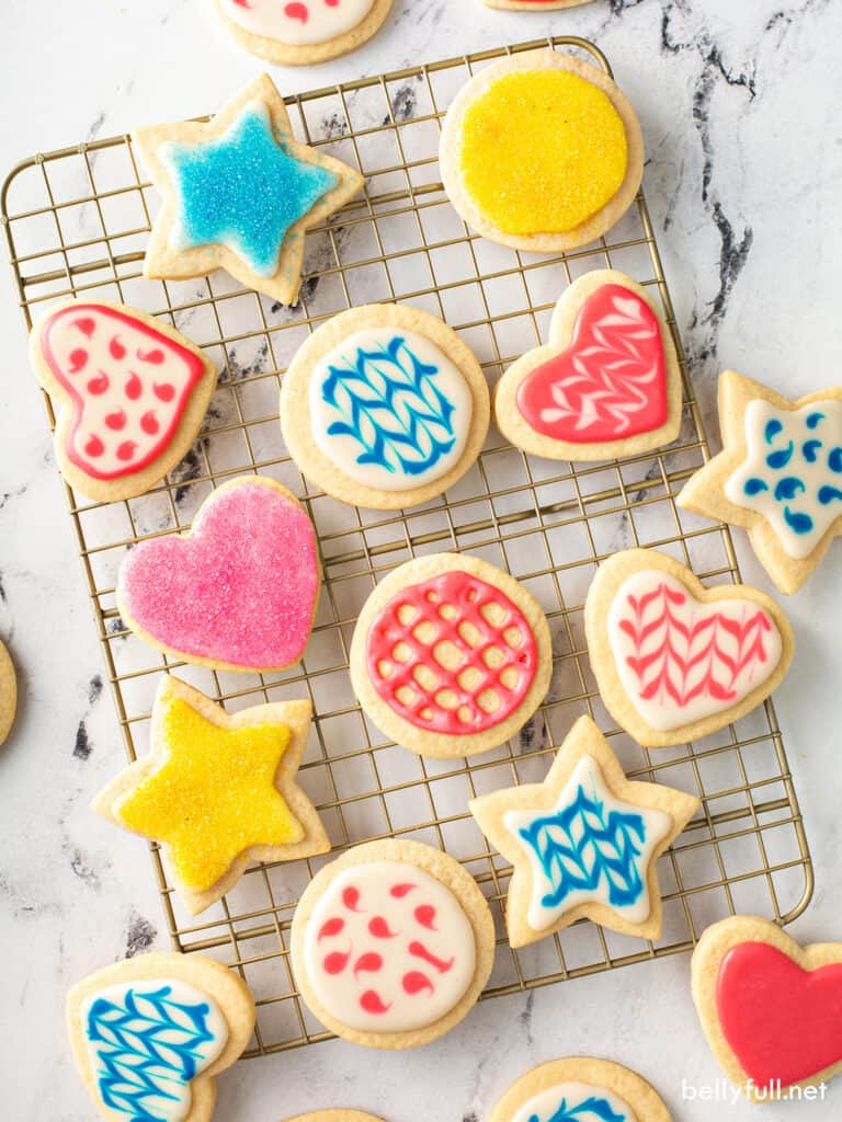 decorated sugar cookies on wire rack with blue, pink, and yellow icing