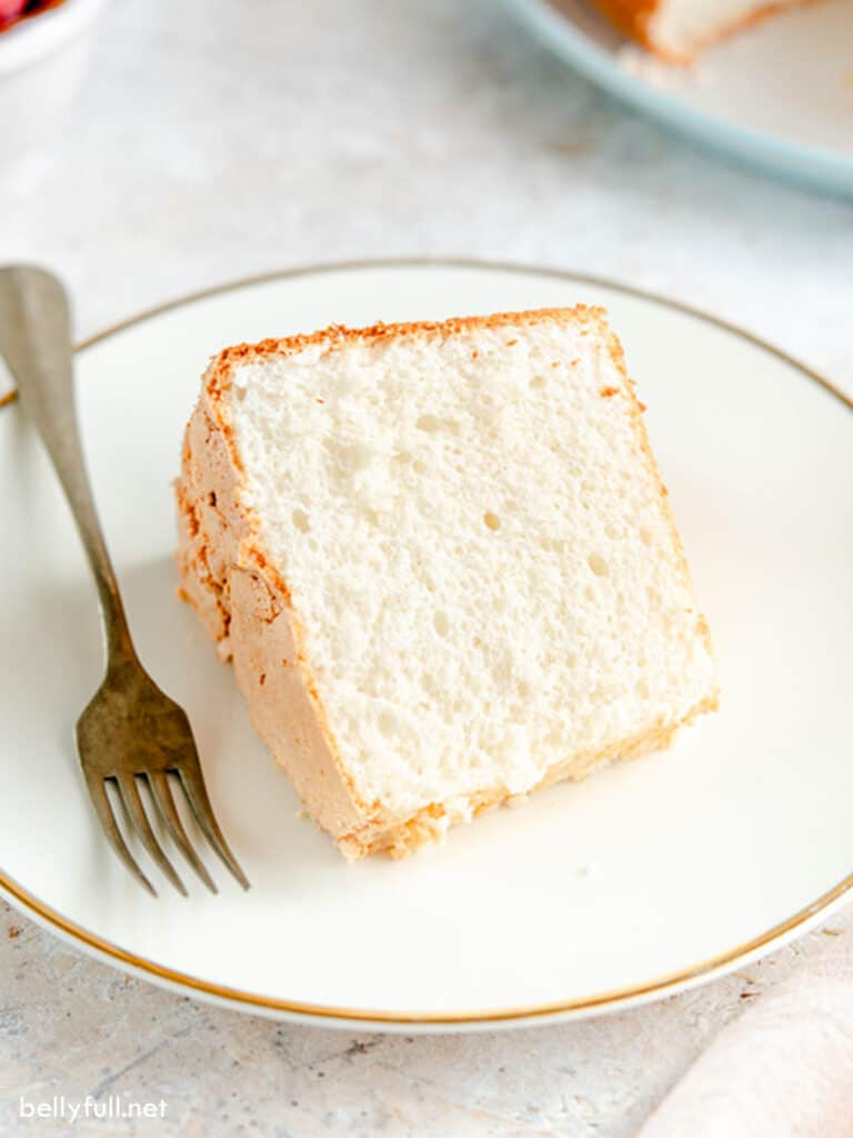 Slice of angel food cake on white plate with fork