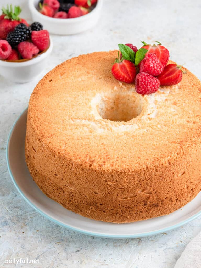whole baked angel food cake on white serving plate