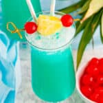 Blue Hawaiian drink garnished with pineapple and a maraschino cherry