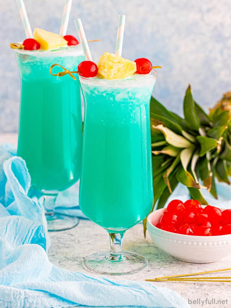 Blue Hawaii drink in hurricane glass with pineapple and cherry garnish