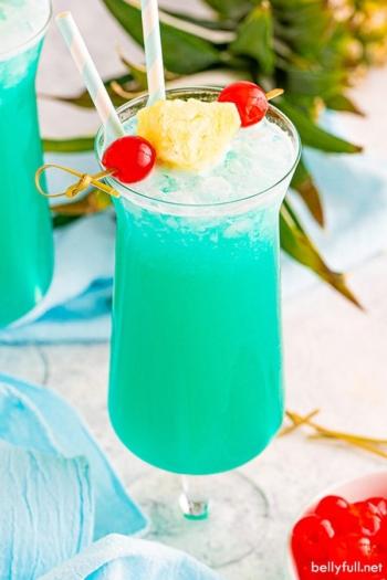 Blue Hawaiian drink in hurricane glass with pineapple garnish